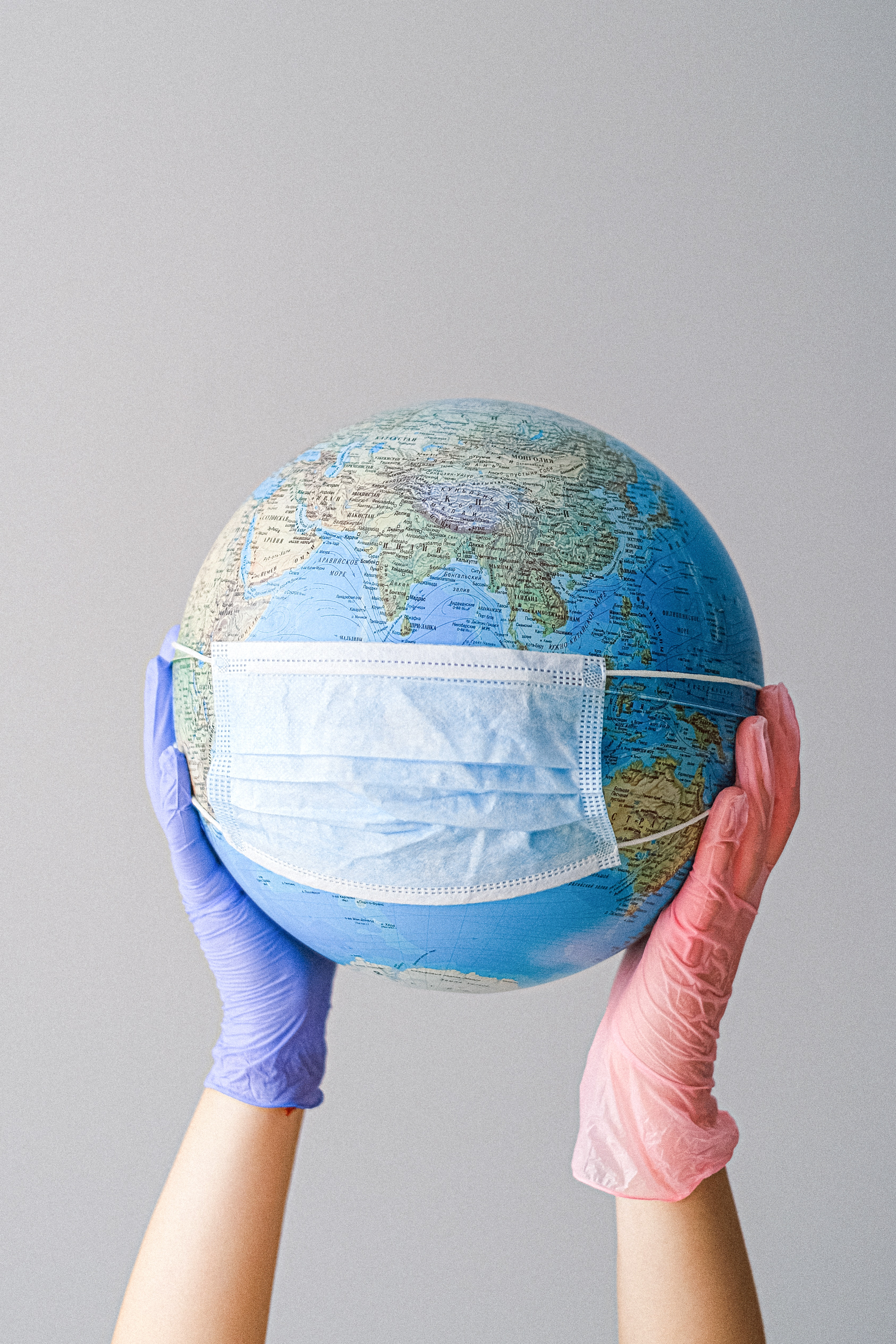 Hands with Latex gloves holding globe with mask